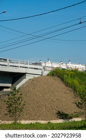 A mound of pebbles at the foot of an automobile overpass. Concrete car overpass in the city center. Concrete overpass with massive concrete supports.