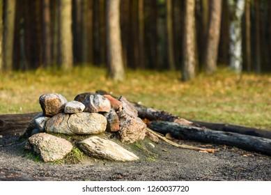 Mound of stones forming a firepit in forest landscape.