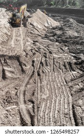Mounds of dirt at construction site. Tractor tread tracks in soil. Motion blurred excavator in background. Vertical composition.
