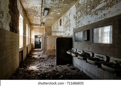 Mounds of hazardous bird poop is visible in sinks at a bathroom inside a long abandoned hospital.
