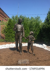 """Mount Airy, North Carolina, USA - July 4, 2020: A statue honors """"The Andy Griffith Show"""" outside the """"Andy Griffith Playhouse"""" depicting the Andy Griffith and Opie characters from the television show."""