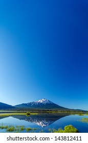 Mount Bachelor being reflected in a lake with most of the image being taken up by beautiful blue sky