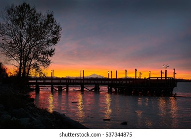 Mount Baker Sunrise, Fraser River. A sliver of sunrise at the No. 3 Road fishing pier in Richmond.  Mount Baker in the background.
