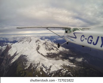 Mount Baker, Washington, United States of America - Sept 22, 2017 - Small airplane, Cessna 172, is flying over a big beautiful volcano. Landmark located East of Vancouver and Northeast of Seattle.