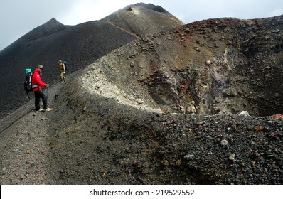 MOUNT CAMEROON, CAMEROON  - CIRCA JUNE, 2008  - Two hikers from Europe resting near Mt.Cameroon volcano crater. Landscape is volcano ash covered by eruption that took place in 2000.