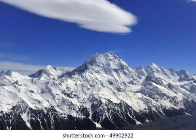 Mount Cook peak against a deep blue sky with puff of white cloud New Zealand