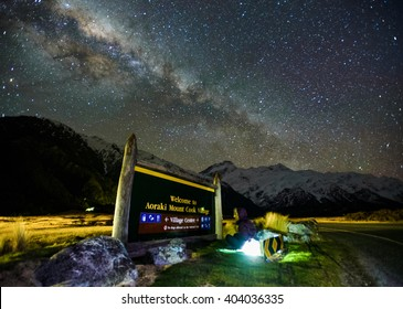 Mount Cook Village Signboard Under Milky Way Galaxy Rising Above Snow Capped Southern Alps Mountain Range At Mount Cook National Park, Canterbury, New Zealand.  Image Noise Due To High ISO