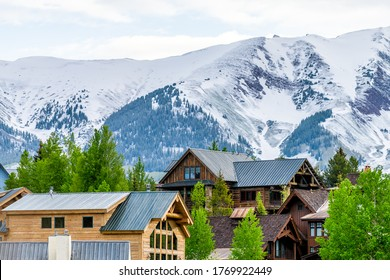 Mount Crested Butte, Colorado village in summer morning with hilldside houses on hills and Aspen green trees closeup