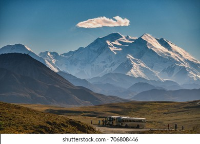 mount denali looms above pulloff from denali national park road, with single lenticular cloud amid clear blue sky