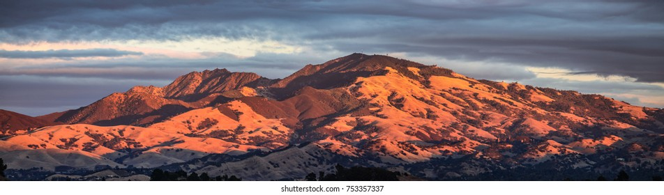 Mount Diablo panorama taken from the West with glowing sun on the mountain during early susnset