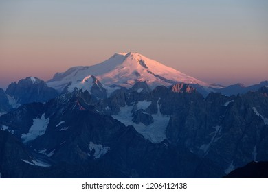 Mount Elbrus, the highest mountain in Europe and a dormant volcano in the Caucasus Mountains in Russia. The first rays of the sun illuminate Elbrus summit at the sunrise, August 2018.