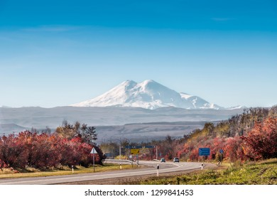 Mount Elbrus is the highest peak of Russia and Europe. Snapshot from a distance of 90 kilometers. In the foreground is the motorway to Kislovodsk. HDR image. Caucasus, Russia.