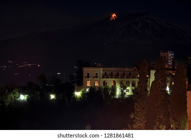 Mount Etna volcano at night showing lava flow over town