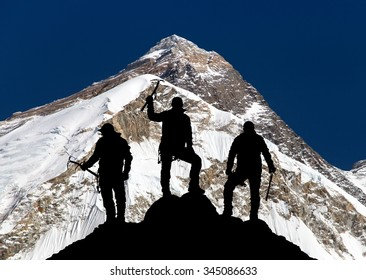 Mount Everest, from Pumo Ri base camp and silhouette of three climbing men with ice axe in hand - trek to everest base camp - Nepal