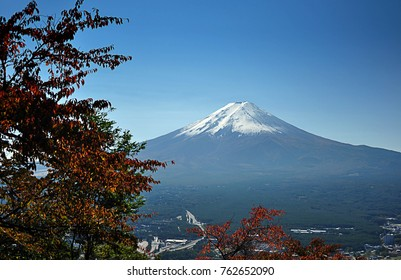 Mount Fuji of Japan in Kawaguchiko town with clear blue sky in broad daylight. Red maple leaves in foreground. Japan famous romantic landmark and tourist attractive.