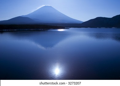 Mount Fuji with the sun reflecting in a blue lake