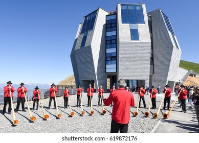 Mount Generoso, Switzerland - 8 April 2017: People playing the alphorn in front of the modern restaurant at Mount Generoso on the Swiss alps