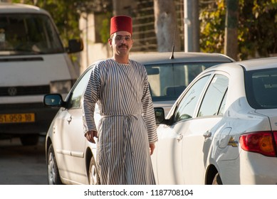 MOUNT GERIZIM DISTRICT, ISRAEL - OCTOBER 14, 2011: Traditional dressed young Samaritan coming to evening prayer at sunset time