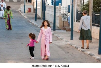 MOUNT GERIZIM DISTRICT, ISRAEL - OCTOBER 14, 2011: Undefined Samaritan small girls walk on the street at sunset time