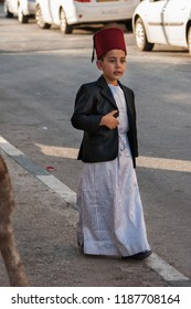 MOUNT GERIZIM DISTRICT, ISRAEL - OCTOBER 14, 2011: Traditional dressed Samaritan boy coming to evening prayer at sunset time