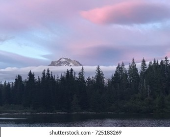 Mount Hood National Forest and Mirror Lake as the sun sets and the clouds light up in color over the peak of the volcanic mountain poking above the tree line during sunset.