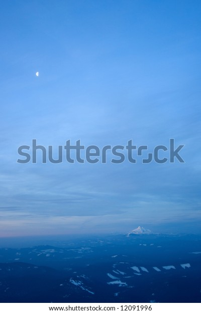 Mount Jefferson stands covered in snow in the distance under a moon as the sun rises