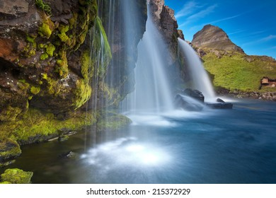Mount Kirkjufell (Church mountain) in the Snaefellsnes peninsula, Iceland (Island), complimented by a waterfall on a beautiful summer day