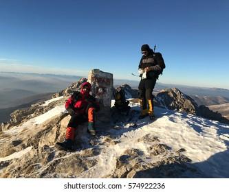 MOUNT KORAB, MACEDONIA - DECEMBER 21: Climbers at top of the Mount Korab (2764 m) on December 21, 2016 in Macedonia. Mount Korab on Macedonia-Albania border and highest mountain of both countries.