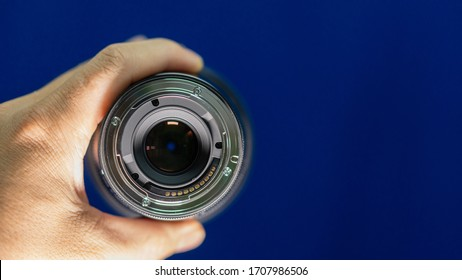 Mount lens connected to the camera in the hand holding the blue background
