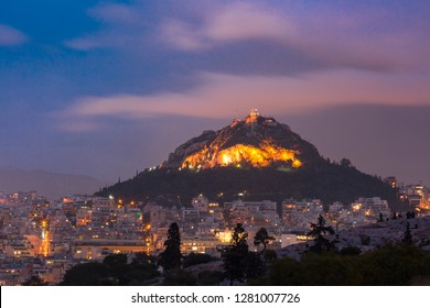 Mount Lycabettus towering above of the roofs of Old Town at sunset in Athens, Greece