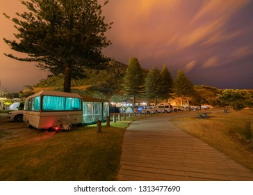MOUNT MAUNGANUI NEW ZEALAND - FEBRUARY 7: Caravans and campers near the base track access walkway at Mount Maunganui Camping ground at night February 7 2019 Mount Maunganui New Zealand