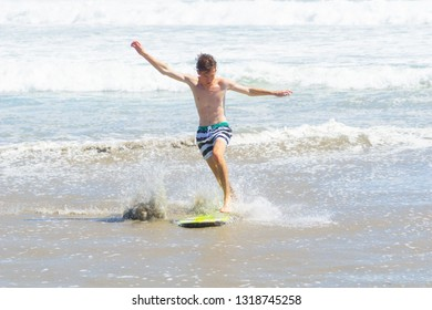 MOUNT MAUNGANUI NEW ZEALAND - FEBRUARY 10: Teenager skim-boarding in shallows on beach arms outstretched for balance February 10 2019 Mount Maunganui