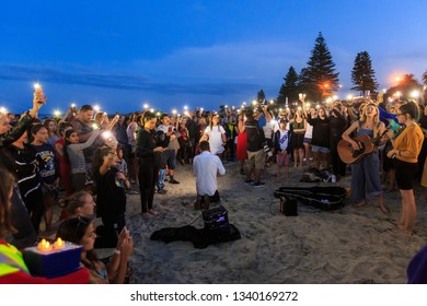Mount Maunganui / New Zealand - March 16 2019: Twilight Beach Vigil For Victims of the March 15 Christchurch Mosque Shootings. The Crowd Hold Up Their Cellphone Torches