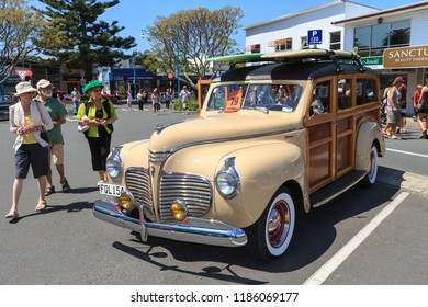 """Mount Maunganui / New Zealand - October 27 2012: People Admire a Pristine 1941 Plymouth Special Deluxe """"Woody"""" Wagon With Two Surfboards on the Roof"""