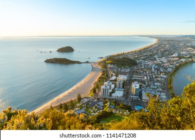 Mount Maunganui stretches out below as sun rises on horizon and falls across ocean beach and buildings below