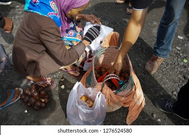 Mount Merapi,Yogyakarta,Indonesia. Taken on November 2018. From above shot for unrecognized old woman salak fruit seller in Mount Merapi is selling the fruit.