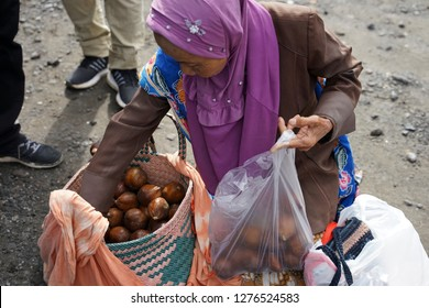 Mount Merapi,Yogyakarta,Indonesia. Taken on November 2018. Photo for close up unrecognized old woman salak fruit seller in Mount Merapi is selling the fruit.