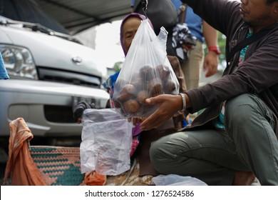 Mount Merapi,Yogyakarta,Indonesia. Taken on November 2018. Photo for unrecognized man is weighing the salak fruit.