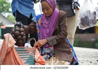 Mount Merapi,Yogyakarta,Indonesia. Taken on November 2018. Photo for unrecognized old woman salak fruit seller in Mount Merapi is selling the fruit.