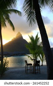 Mount Otemanu in Bora Bora at sunset framed by palm trees and table and chairs