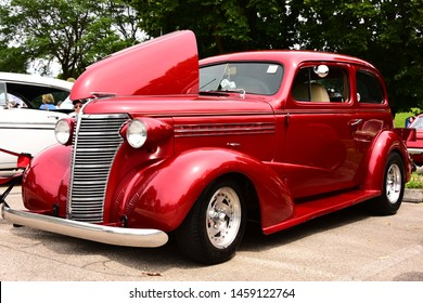 Mount Pleasant, Wisconsin / USA - July 21, 2019: An outstanding beautiful red metallic 1938 Chevrolet Master Deluxe with hood raised images in three quarter front view at the Quarry Lake Car Show.