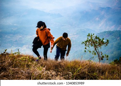 Mount Polis, Philippines - February 24, 2019: Two hikers scaling the last few steps before reaching the summit of the mountain. Concept photo for perseverance and overcoming challenges.