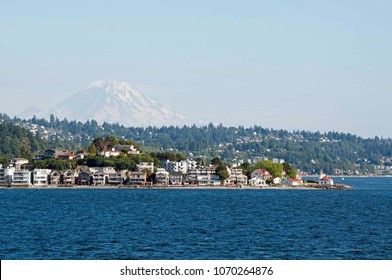 Mount Rainier looms large behind Alki Point Lighthouse in Seattle, WA, USA, photographed from Puget Sound.