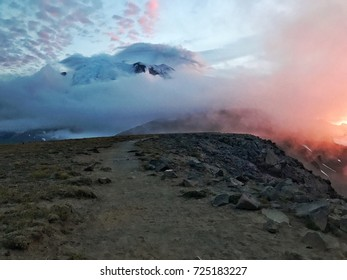 Mount Rainier National Park during a cloudy sunset shows it's peak in a real in the clouds while stunning colors engulf the scene as a trail leads the eye towards the mountain itself.