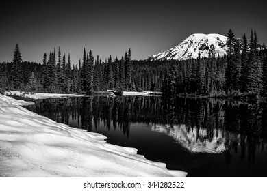 Mount Rainier reflecting in a high mountain lake during the thawing snow of early springtime / Mount Rainier Reflection / Mount Rainier in Early Springtime