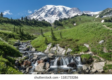 Mount Rainier towers above a waterfall in Mount Rainier National Park, Washington.