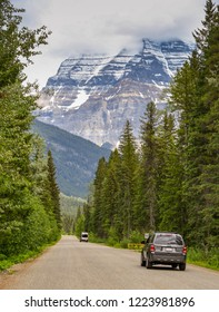 MOUNT ROBSON, BRITISH COLUMBIA, CANADA - JUNE 2018: Car driving down a road in the Mount Robson Provincial Park in British Columbia, Canada. The mountain dominates the background.