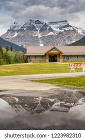 MOUNT ROBSON, BRITISH COLUMBIA, CANADA - JUNE 2018: Exterior view of the Mount Robson Visitor Centre with the mountain in the background reflected in a large pool of water in the foreground.