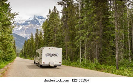MOUNT ROBSON, BRITISH COLUMBIA, CANADA - JUNE 2018: Camping trailer being towed along a road in the Mount Robson Provincial Park in British Columbia, Canada. The mountain dominates the background.