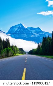Mount Robson (Canada) is bigger than the surrounding clouds. The road to the mountain seems endless. Typical yellow lines on the highway lead to the wonderful Mountain.